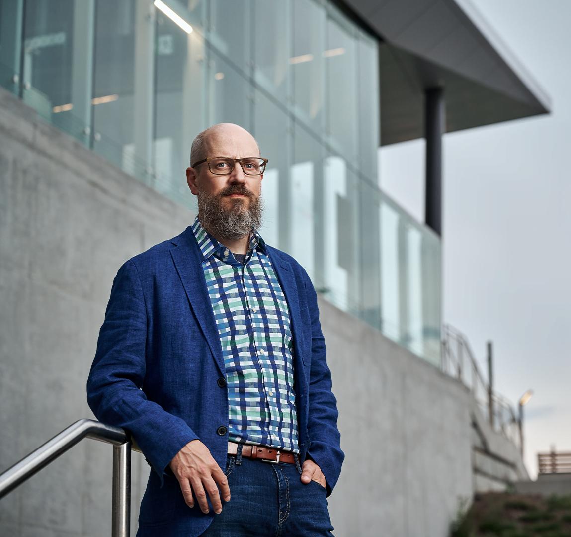 Portrait of Michael Spratt leaning on metal railing in front of industrial building
