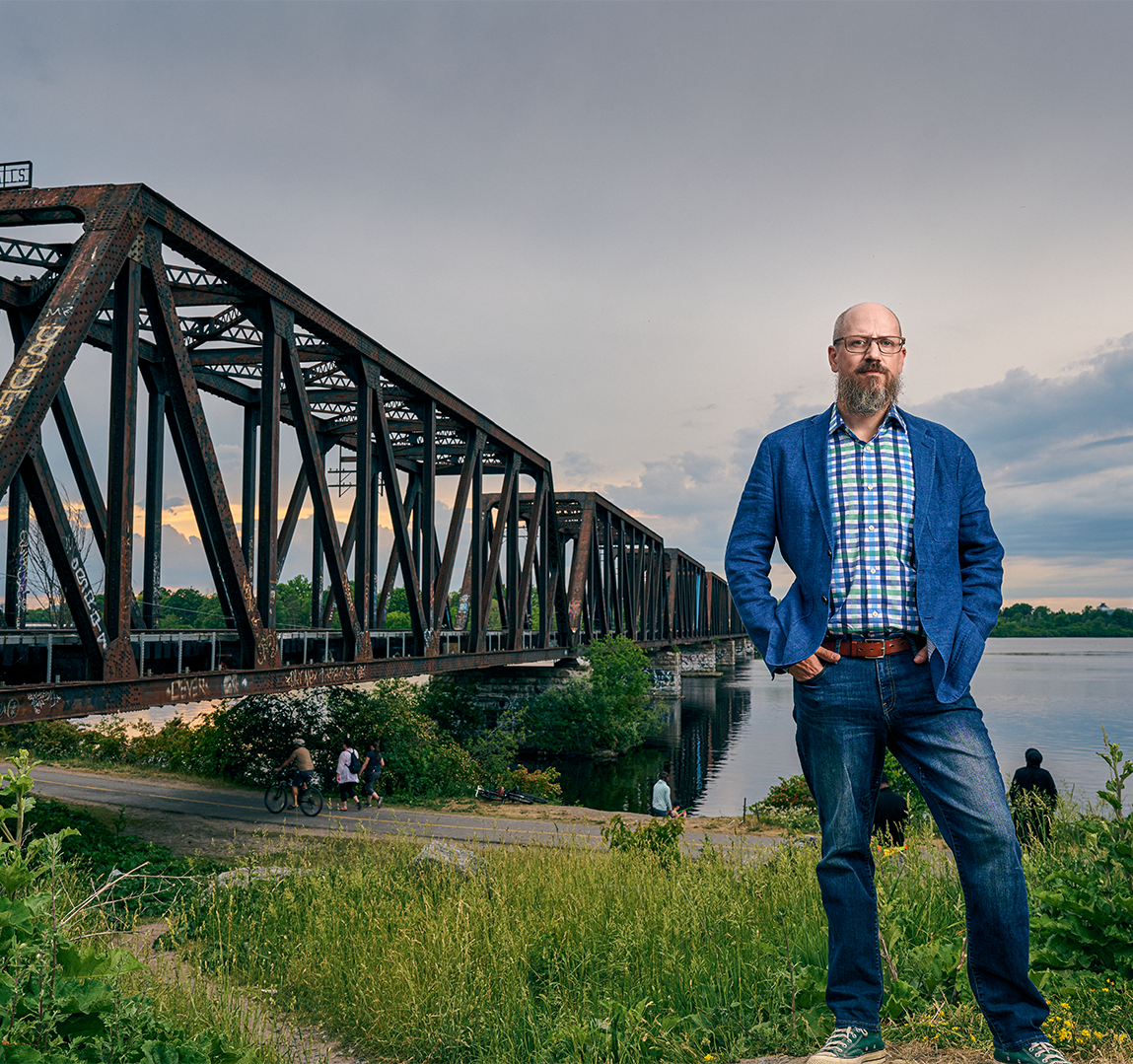 Portrait of Michael Spratt standing on grass in front of industrial bridge and water